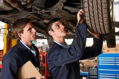 Mecánico And Trainee Working en el coche junto Foto de archivo libre de regalías