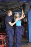 Mecánico y aprendiz que trabajan en el coche Foto de archivo libre de regalías