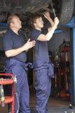 Mecánico y aprendiz que trabajan en el coche Imagen de archivo libre de regalías