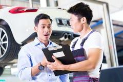 Mecánico y cliente de coche en taller auto asiático Foto de archivo
