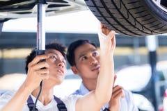 Mecánico y cliente de coche en taller auto asiático Fotografía de archivo libre de regalías