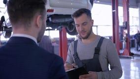 Mecánico y propietario de coche acertados, hombres del trato que sacuden las manos en el fondo del automóvil en la elevación metrajes