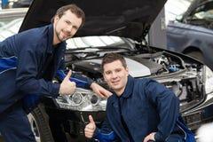 Mecánicos de automóviles felices. Foto de archivo libre de regalías