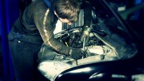 Mecánicos de coche con una llave inglesa que comprueba el motor debajo de la capilla en la gasolinera del coche almacen de metraje de vídeo