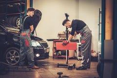 Mecánicos de coche profesionales que examinan la lámpara de la linterna del automóvil en servicio de reparación auto Fotos de archivo libres de regalías