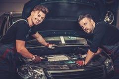 Mecánicos de coche que comprueban debajo de la capilla en servicio de reparación auto Fotos de archivo libres de regalías