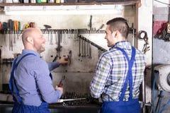 Mecánicos felices en un taller de reparaciones Foto de archivo