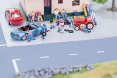 Mecánicos miniatura que reparan un coche y un tractor de granja Fotografía de archivo
