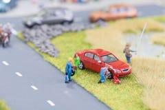 Mecánicos miniatura que substituyen un neumático plano en el borde de la carretera Fotos de archivo