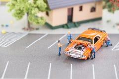 Mecánicos miniatura que trabajan en un coche Foto de archivo