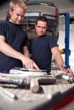 Mecánicos que miran orden de trabajo Fotos de archivo