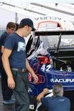 Mecánicos que reparan el coche de carreras de Acura Imagen de archivo libre de regalías