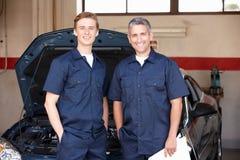 Mecánicos que se colocan delante del coche Imagen de archivo libre de regalías