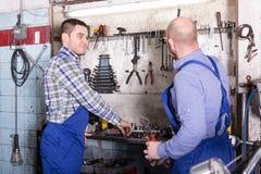 Mecánicos que trabajan en el taller Fotos de archivo libres de regalías