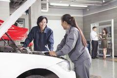 Mecánicos y clientes en taller de reparaciones auto Imagen de archivo