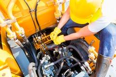 Mecânico asiático que repara o veículo da construção Imagens de Stock