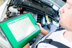 Mecânico com a ferramenta diagnóstica na oficina do carro fotos de stock royalty free
