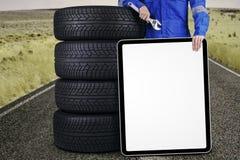 Mecânico com pneus e uma placa fora Imagem de Stock