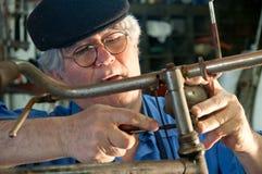 Mecânico da bicicleta que repara um farol Foto de Stock