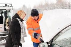 Mecânico da mulher que olha sob a neve da capa do carro Foto de Stock