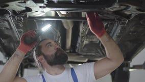 Mecânico de carro farpado que inspeciona a suspensão ou os freios no carro com a lâmpada do automóvel levantado na estação do ser video estoque
