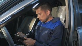 Mecânico de carro profissional que trabalha no serviço de reparação de automóveis moderno e que verifica o motor Fotos de Stock Royalty Free