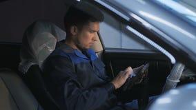 Mecânico de carro profissional que trabalha no serviço de reparação de automóveis moderno e que verifica o motor Fotos de Stock