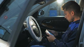 Mecânico de carro profissional que trabalha no serviço de reparação de automóveis moderno e que verifica o motor Foto de Stock Royalty Free