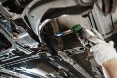 Mecânico de carro que inspeciona a roda de carro e o detalhe da suspensão do reparo Automóvel levantado na estação do serviço de  imagens de stock