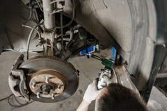 Mecânico de carro que inspeciona a roda de carro e o detalhe da suspensão do reparo Automóvel levantado na estação do serviço de  foto de stock