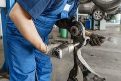 Mecânico de carro que inspeciona a roda de carro e o detalhe da suspensão do reparo Automóvel levantado na estação do serviço de  fotografia de stock royalty free