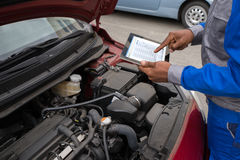 Mecânico With Digital Tablet ao examinar o carro Foto de Stock Royalty Free