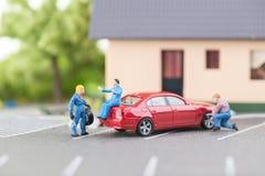 Mecânico diminuto que muda um pneumático puncionado imagens de stock