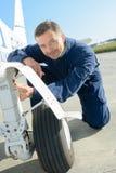 Mecânico do retrato que trabalha no trem de aterrissagem do ` s dos aviões Fotografia de Stock Royalty Free