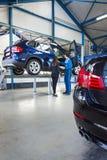 Mecânico e cliente na garagem fotografia de stock royalty free