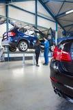 Mecânico e cliente na garagem fotos de stock