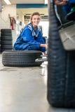 Mecânico fêmea feliz Changing Car Tire na loja do automóvel foto de stock royalty free