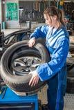 Mecânico fêmea Mounting Car Tire em Rim In Garage fotografia de stock royalty free