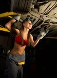 Mecânico fêmea novo bonito que inspeciona o carro na loja de reparação de automóveis Mecânico 'sexy' Fotografia de Stock Royalty Free