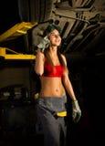 Mecânico fêmea novo bonito que inspeciona o carro na loja de reparação de automóveis Mecânico 'sexy' Foto de Stock Royalty Free