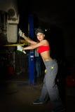 Mecânico fêmea novo bonito que inspeciona o carro na loja de reparação de automóveis Mecânico 'sexy' Fotos de Stock Royalty Free