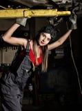 Mecânico fêmea novo bonito que inspeciona o carro na loja de reparação de automóveis Mecânico 'sexy' Imagem de Stock Royalty Free