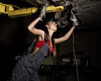 Mecânico fêmea novo bonito que inspeciona o carro na loja de reparação de automóveis Mecânico 'sexy' Imagens de Stock