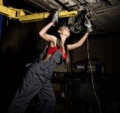 Mecânico fêmea novo bonito que inspeciona o carro na loja de reparação de automóveis Mecânico 'sexy' Imagens de Stock Royalty Free