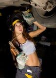 Mecânico fêmea novo bonito que inspeciona o carro na loja de reparação de automóveis O soldador da menina é preparado para conect Imagem de Stock Royalty Free