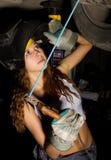 Mecânico fêmea novo bonito que inspeciona o carro na loja de reparação de automóveis O soldador da menina é preparado para conect Fotografia de Stock Royalty Free
