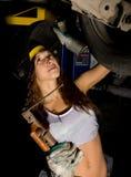 Mecânico fêmea novo bonito que inspeciona o carro na loja de reparação de automóveis O soldador da menina é preparado para conect Imagens de Stock
