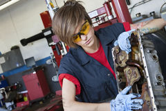 Mecânico fêmea novo que trabalha na peça de maquinaria do automóvel na oficina foto de stock royalty free
