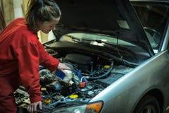 Mecânico fêmea que enche o óleo em um carro Fotografia de Stock