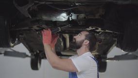 Mecânico farpado bem sucedido que inspeciona a suspensão ou os freios no carro com a lanterna elétrica do automóvel levantado no  filme